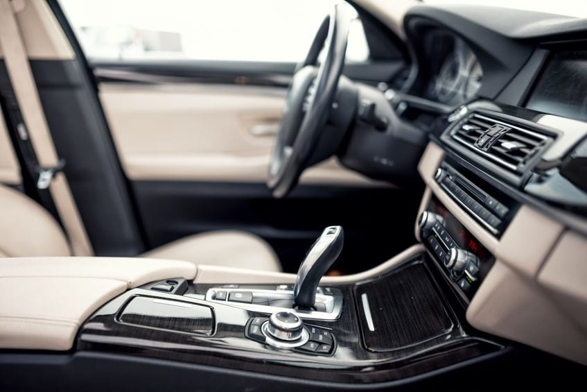 Modern beige and black interior of modern car, close-up details of automatic transmission and gear stick against steering wheel background and dashboard.
